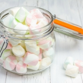 Colorful marshmallows in glass jar on light wooden background closeup