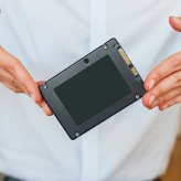 Hands holding fast flash SSD - solid state drive